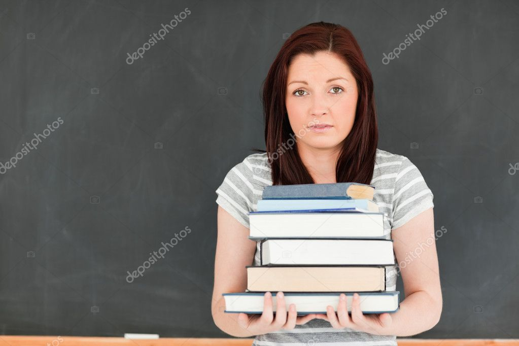 Cute young woman bringing heavy books in a classroom — Stock Photo #10601836