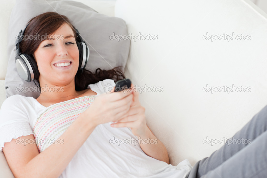 Attractive brunette woman writing a text on her mobile while lying on a sofa in the living room  Stock Photo #10601965