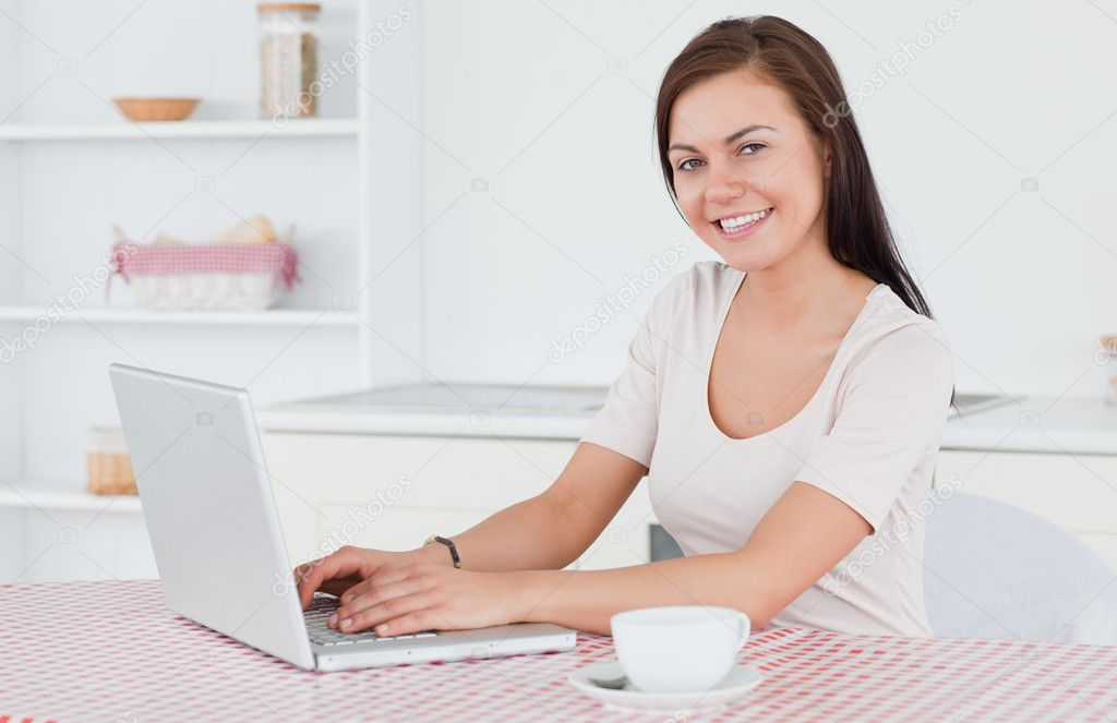 Brunette using her laptop and having a tea in her kitchen — Stock Photo #10603148