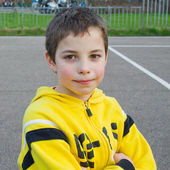 Cute teenage boy in a yellow hoodie in the playground — Stock Photo