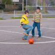 Two boys kicking football on the sports playground — Stock Photo