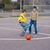 Two boys kicking football on the sports playground — Stock Photo