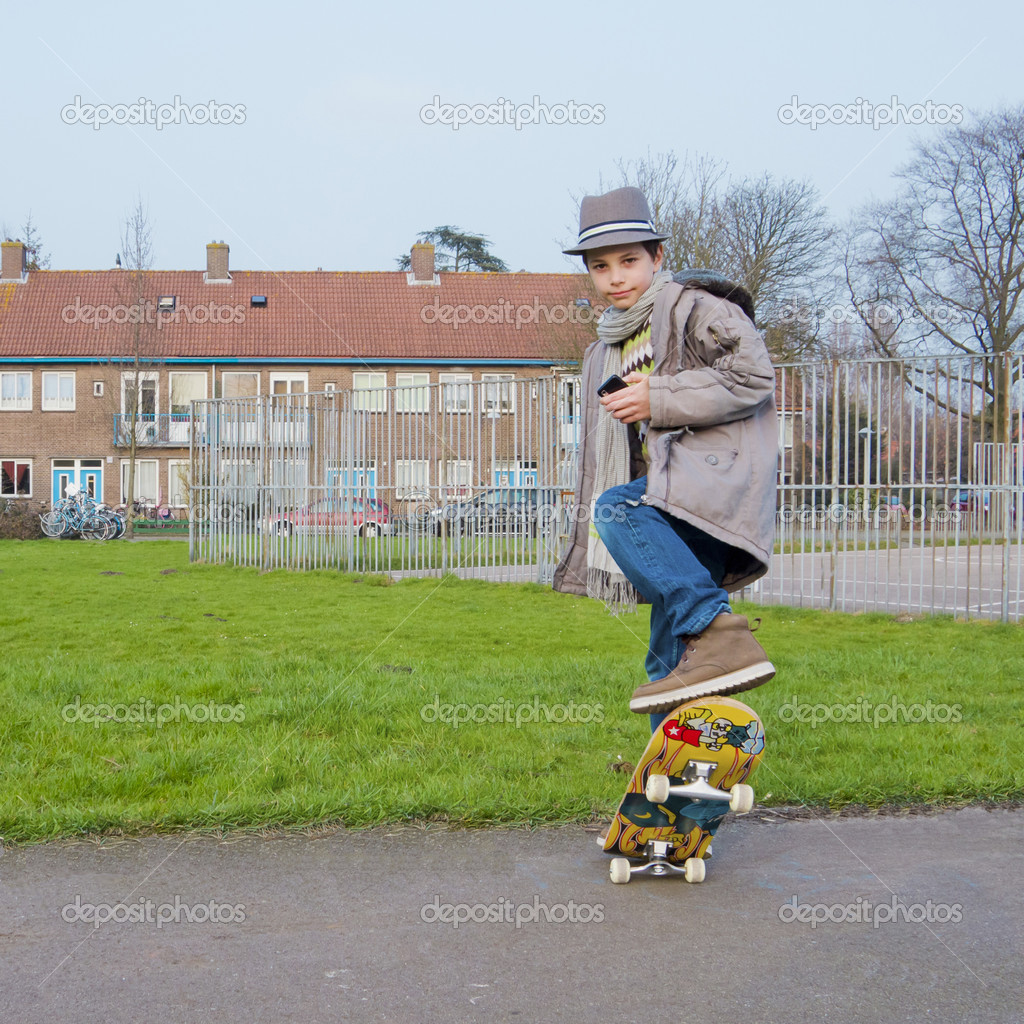 Cute teenage boy with mobile phone doing stunts on a - Skateboard mobel ...