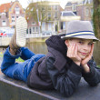 Stock Photo: Funny teenage boy lying on parapet at park