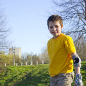 Smiling teenage boy in roller-blading protection kit in a skate — Stock Photo