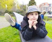 Divertente ragazzo sdraiato sul parapetto al parco — Foto Stock
