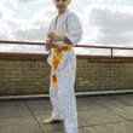 Judoka teen boy training judo on the sky background — Stock Photo