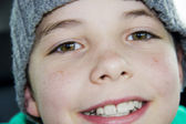 Closeup of cute young teen boy in hat smiling — Stock Photo