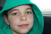 Closeup of cute young teen boy in green hood — Stock Photo