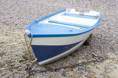 Blue and white boat on the shingle beach — Stock Photo