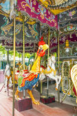 Colorful horses and cock in vintage carousel — Stock Photo
