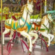 Two colourful horses in a vintage (old fashioned) carousel - Stok fotoğraf