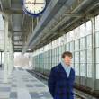 A man waiting for a train under a clock — Stock Photo