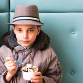 Cute teenage boy eating ice cream with chocolate topping — Stock Photo