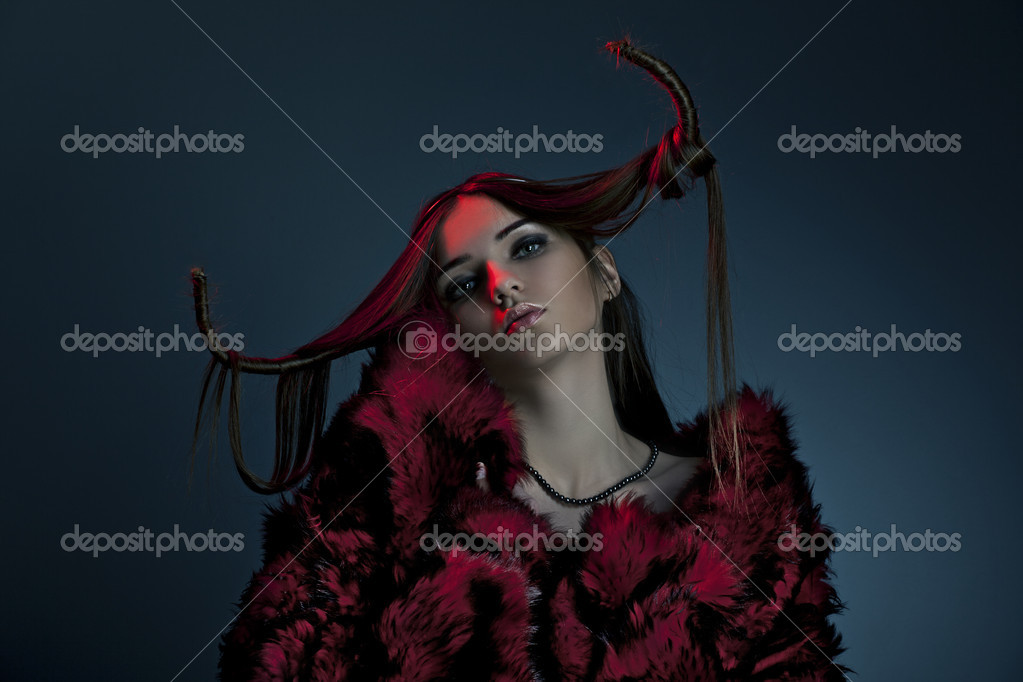 Portrait of a beautiful woman wearing fur on a dark background  Stock Photo #10409225