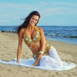 Beautiful womsitting on sand near beach — Stock Photo #10016540