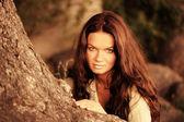 Low contrast portrait of woman recline on tree — Stock Photo