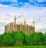 Building under construction and trees — Stock Photo