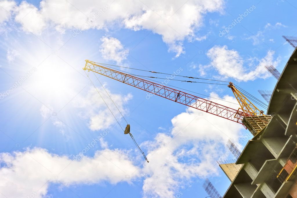 Building with elevating crane and sky with sun on background — Stock Photo #10016728
