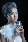 Portrait of woman with creative makeup and wineglass — Photo
