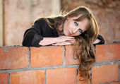 Sad girl recline on brick wall — Stock Photo