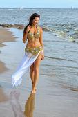Beautiful woman walking on beach — Stock Photo