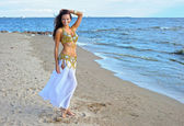 Beautiful woman in white exotic dress near sea — Stock Photo