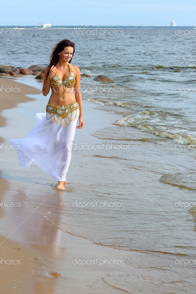 Beautiful young girl walking on the beach  Stock Photo #10472284
