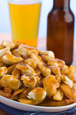 Poutine with beer — Stock Photo