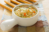 Chicken rice soup with bread stick — Stock Photo