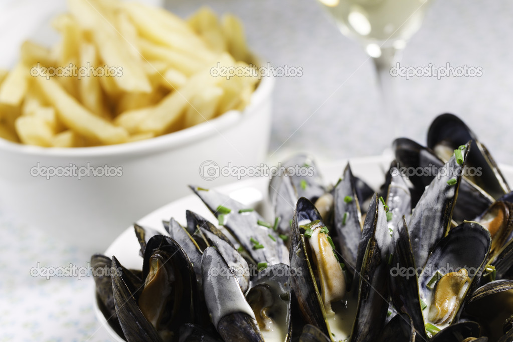 Mussel with white wine sauce and french frie  on a plate. Very shallow depth of field. — Stock Photo #9927047