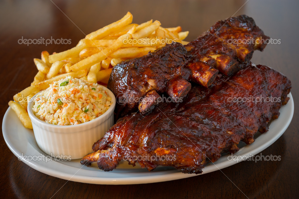 Pork ribs back with french fries and coleslaw salad on the side. Shallow depth of field. — Stock Photo #9928363