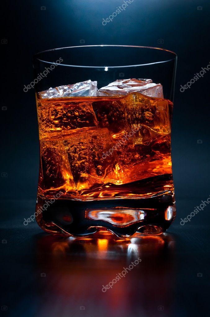 A close up studio shot of an single alcoholic drink on the rocks in a dark room — Stock Photo #9812676