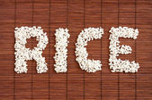 "The word ""Rice"" from rice on a Dark Bamboo Mat background — Stock Photo"