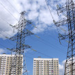 Transmission line against the blue sky with clouds and modern apartment houses — Stockfoto