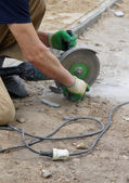 The worker cuts a stone the electric tool — Foto Stock