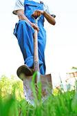 El hombre de overol azul oscuro excava una pala un terreno — Foto de Stock