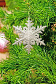 Artificial snowflake on a green fur tree — Stock Photo