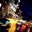 Moving car through city at night — Stock Photo