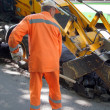 The worker shifts a shovel asphalt - Stock Photo