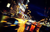 Moving car through city at night — Stock Photo