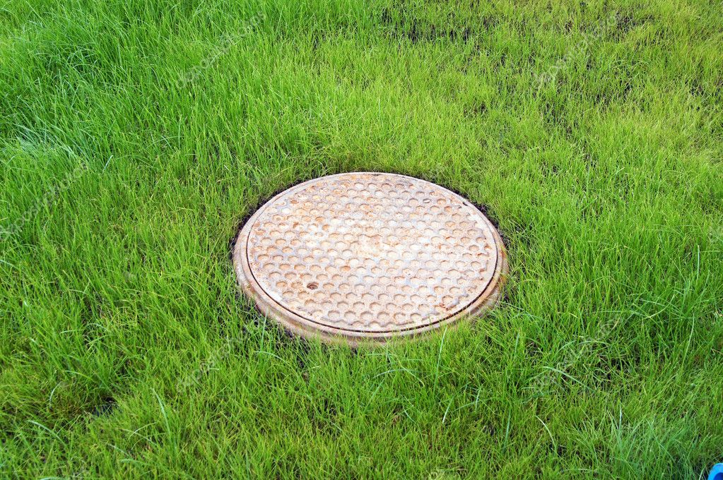 Sewer well on a green lawn — Stock Photo #9950849