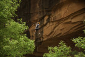 Rock climber rapelling down orange cliff — Stock Photo