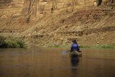 Woman paddling canoe on desert river — Stock Photo