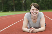 Young woman stretching on running track before workout — Stock Photo