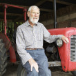 Organic Farmer Sitting Next To Old Fashioned Tractor - Stock Photo