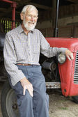 Organic Farmer Sitting Next To Old Fashioned Tractor — Stock Photo