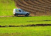 在绿色的原野上的白色车 — 图库照片