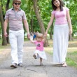 Young family walking in the park — Stock Photo
