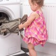 Baby reaching for the washed things - Stock Photo